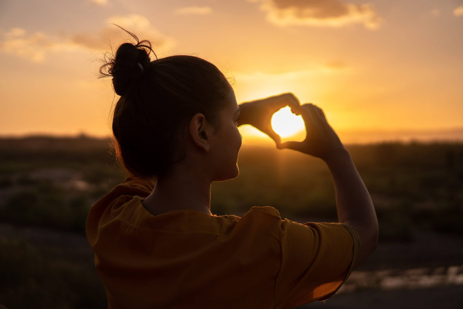 A girl forming a heart with her fingers in a sunset
