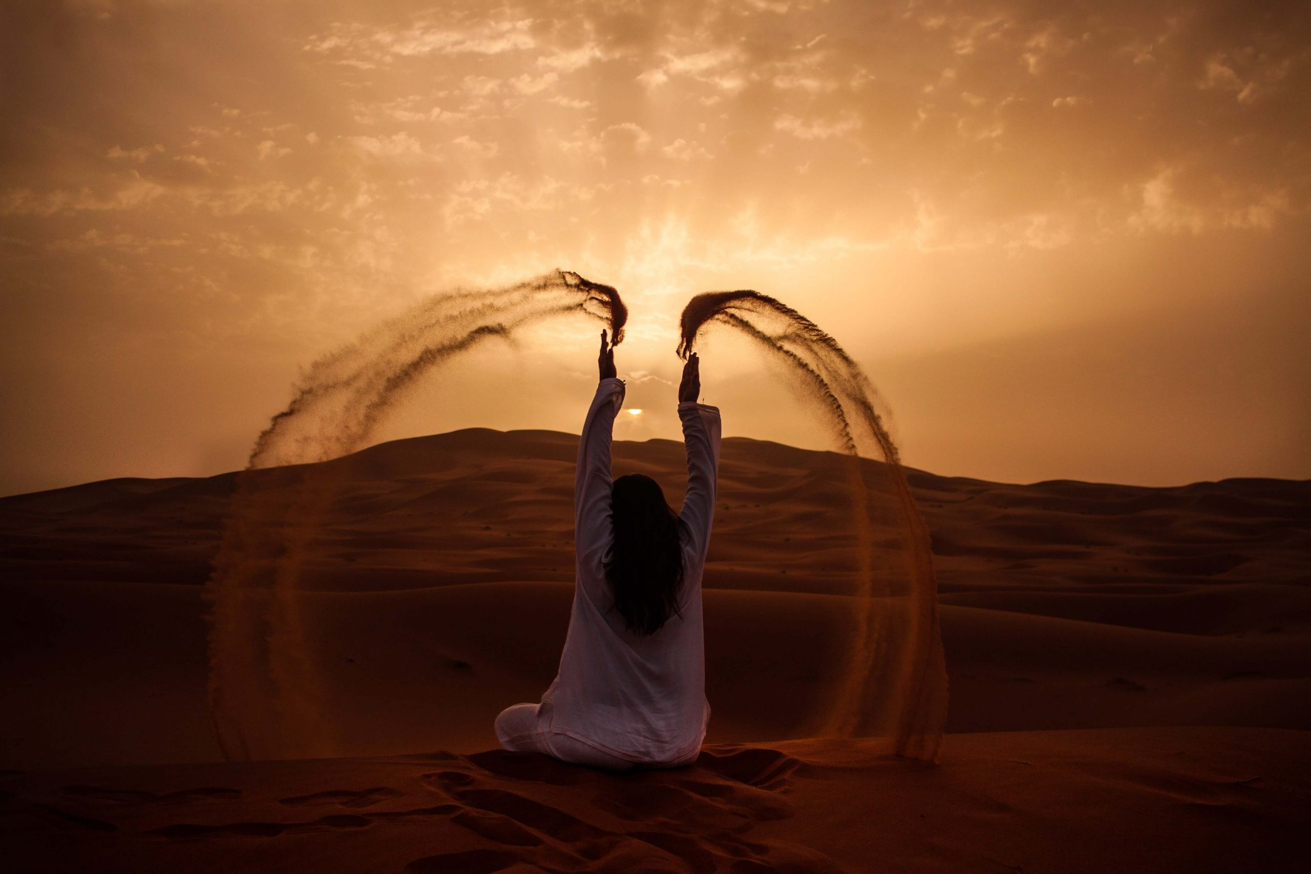 a lady sitting on a sand dune throwing sand into the airt